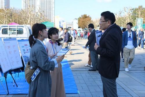 全国軽自動車協会連合会の堀井仁会長に説明する学生